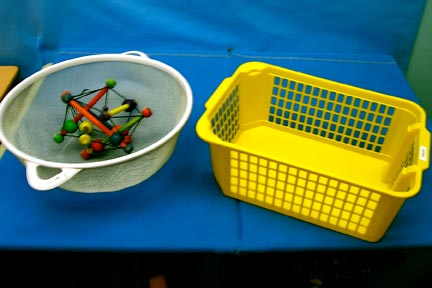 a white circular basket with a geometric object inside and an empty yellow basket are placed on a blue cloth on a tableAn example of an anticipation calendar with high contrast baskets set against blue background material.